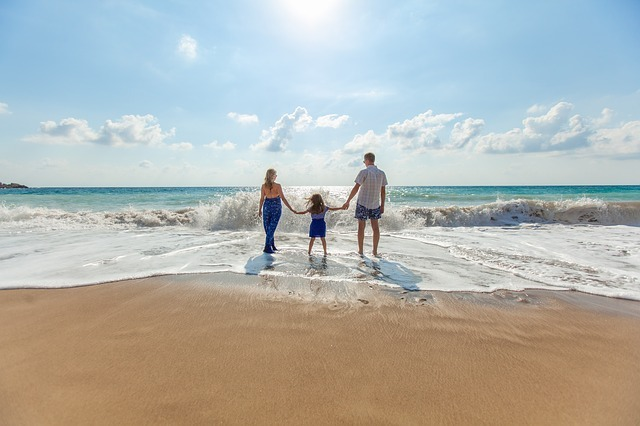 Familia feliz de Vacaciones en una paradisíaca playa, disfrutando de unas vacaciones con niños