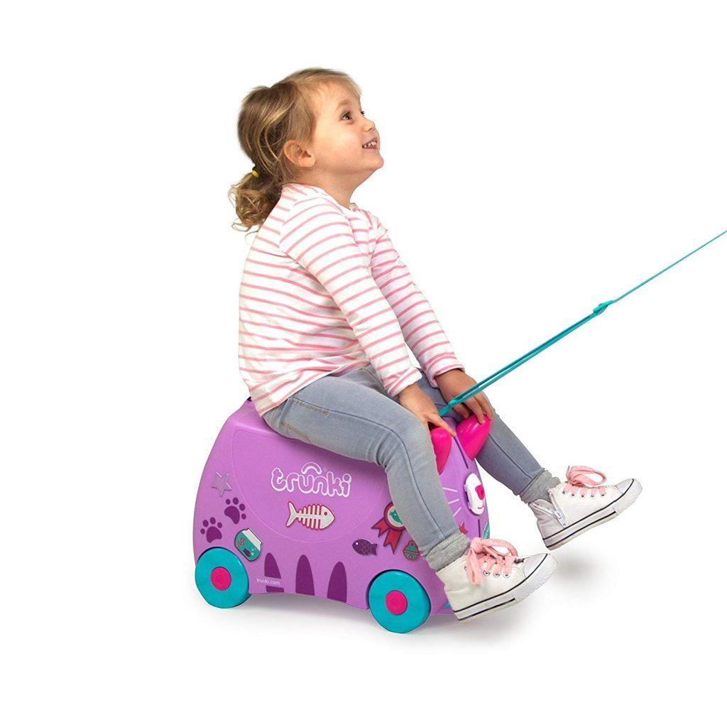 Niña Feliz y Divertida Montada en su Maleta Infantil Correpasillos Tipo Trolley de la Marca Trunki